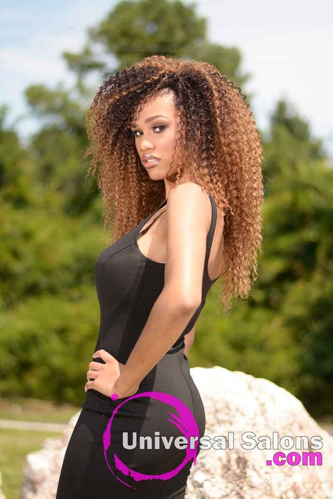 Model Standing With Long Curly Sew In Hairstyle