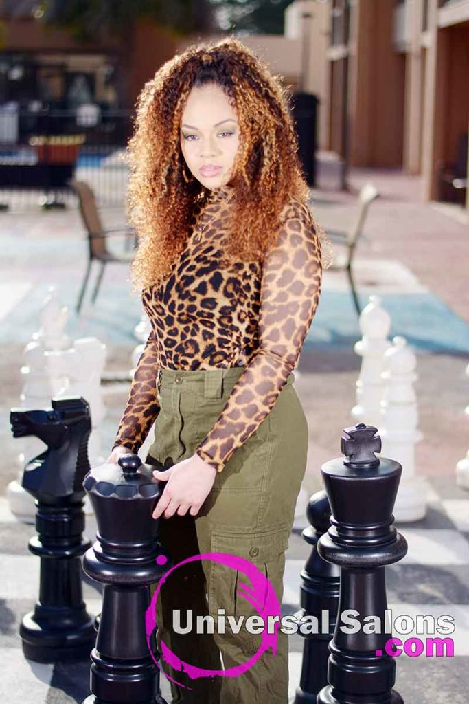 Model Holding Chess Piece With Bohemian Curls