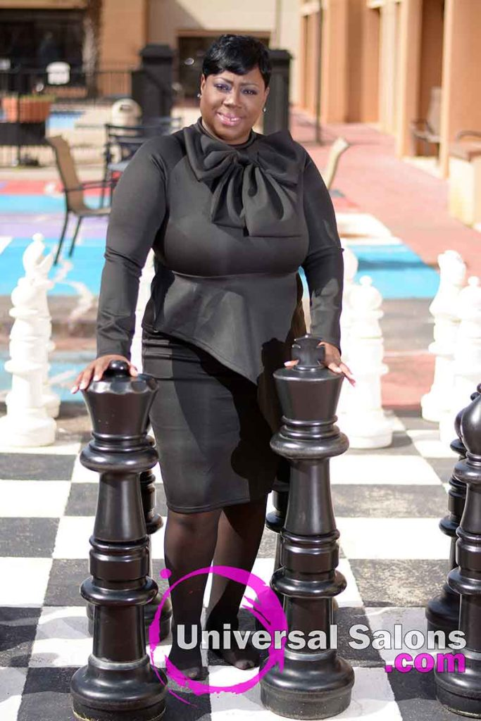 Model Standing Behind Chess Pieces With Short Quick Weave